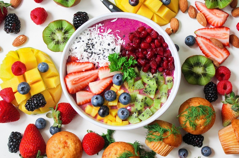 Mix of fruit in a bowl with yoghurt surrounded by fruit and muffins
