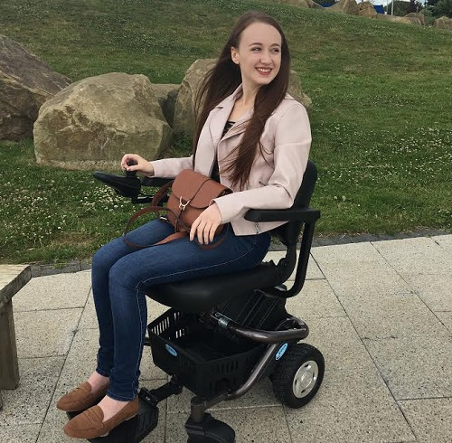 Pippa in her wheelchair outside by a grassy bank wearing jeans and a pale pink jacket