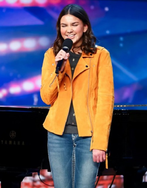 Sirine Jahangir standing on the Britain's Got Talent stage holding a microphone