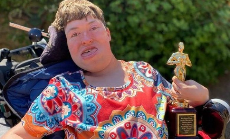 Stephanie-Castelete-Tyrrell-in-her-wheelchair-holding-her-award-in-the-garden