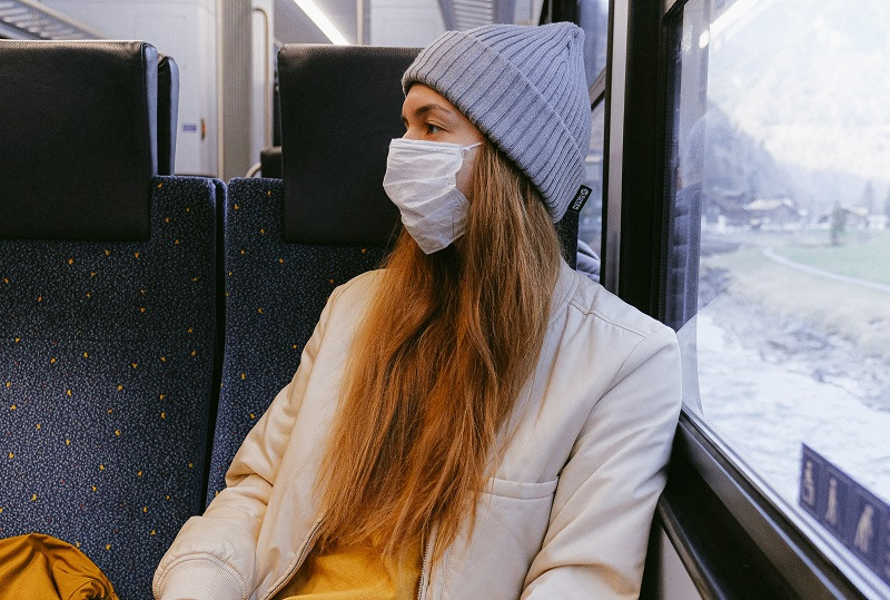 Woman on a train wearing a face mask wearing a grey knitted had and cream coat