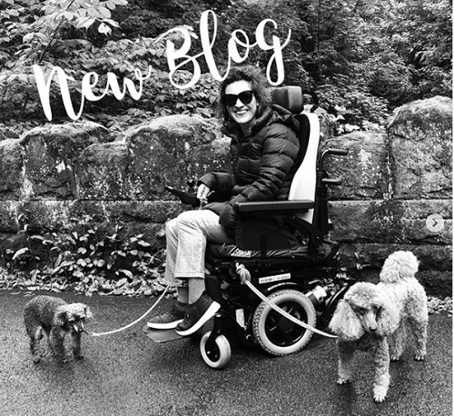 Black and white image of Lucy Reynolds in her wheelchair with her two dogs and the words new blog across the top