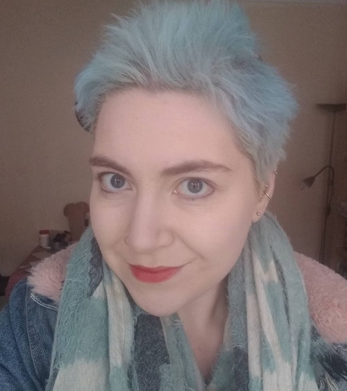 Close up of Daisy Holder with short pale blue hair, blue scarf and denim jacket