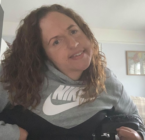 Close up of Georgina Moore in her wheelchair with a grey jumper and brown curly hair