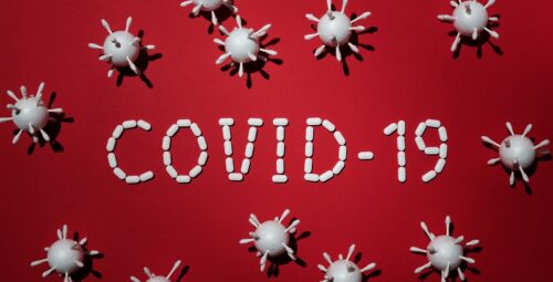 Covid-19 in white words on a red background with images of virus particles around it