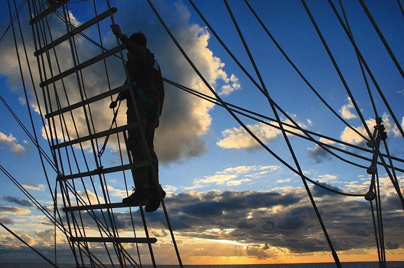 Image taken by blind photographer Roesie Percy of a man stanging on the ropes on a boat in the English Channel at sunset