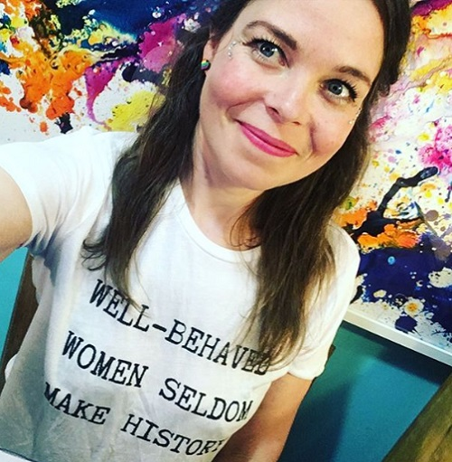 Juliette Burton wearing a white T-shirt with the words well-behaved women seldom make history