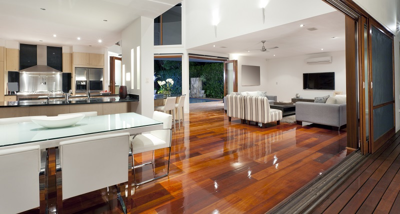 Large open-plan kitchen, dining room and living room with white futnirue and wooden flooring