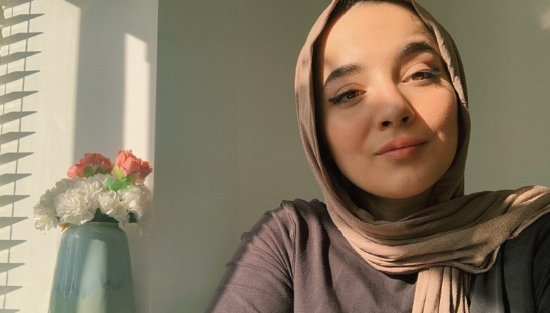 Lina Bettayeb wearing a beige hijab and grey top sat by a window with a vase containing pink and white flowers