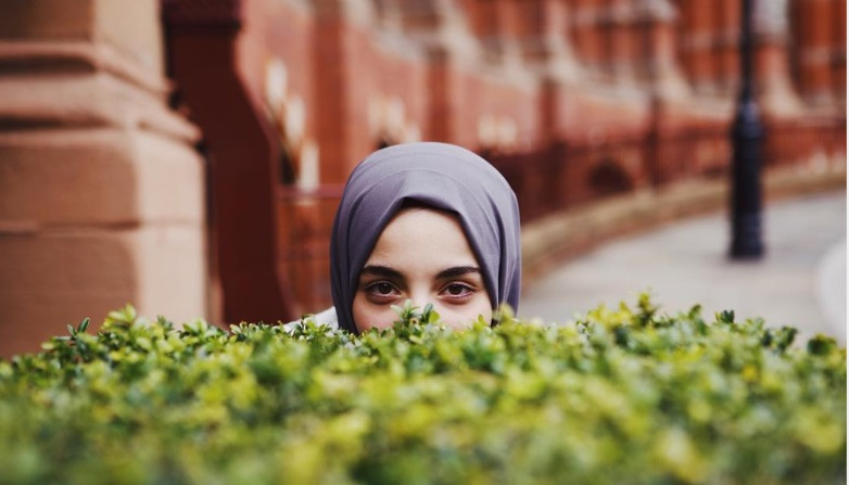 Lina Bettayeb wearing a grey hijab looking over a hedge with only her eyes showing