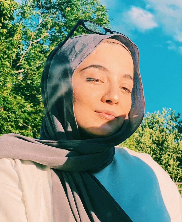 Lina Bettayeb wearing a grey hijab stood in front of a tree looking into the distance.