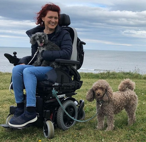 Lucy Reynolds in her wheelchair with her two dogs on a cliff top above the sea