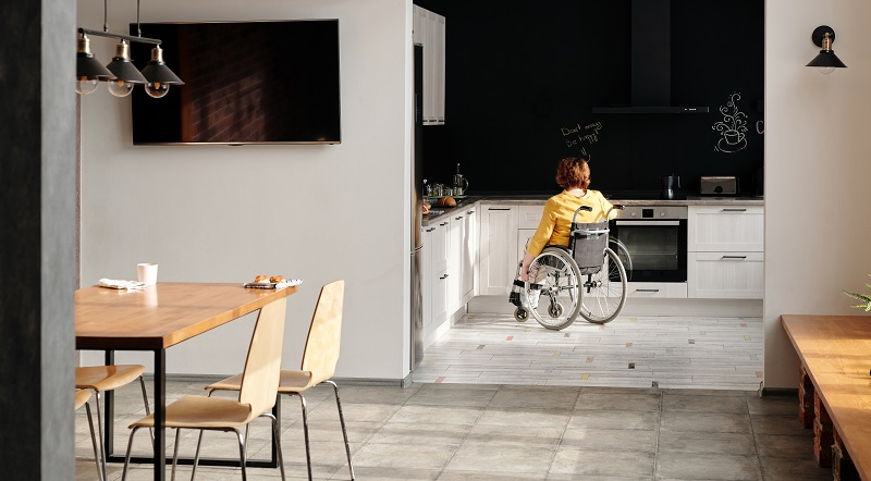 Open plan dinning room and white kitchen with a woman in a wheelchair