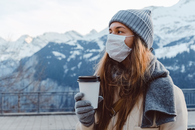 Woman in a grey scarf and cream coat stood in front of snow-covered mountains with a face mask on holiday a cup of coffee