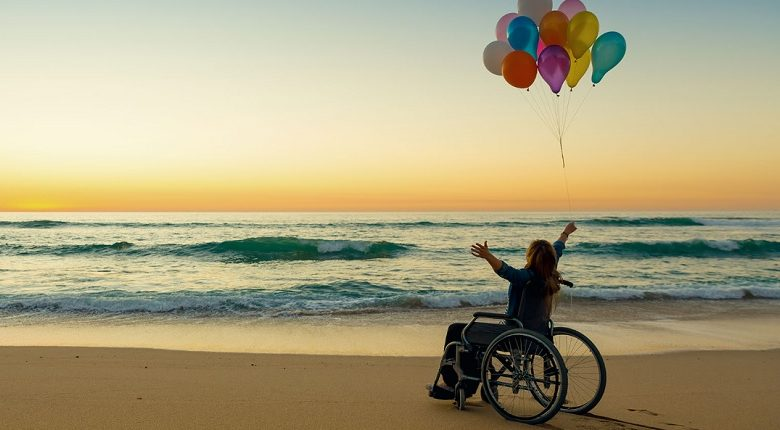 Woman in a wheelchair with her arms in the air on a beach at sunset holding balloons