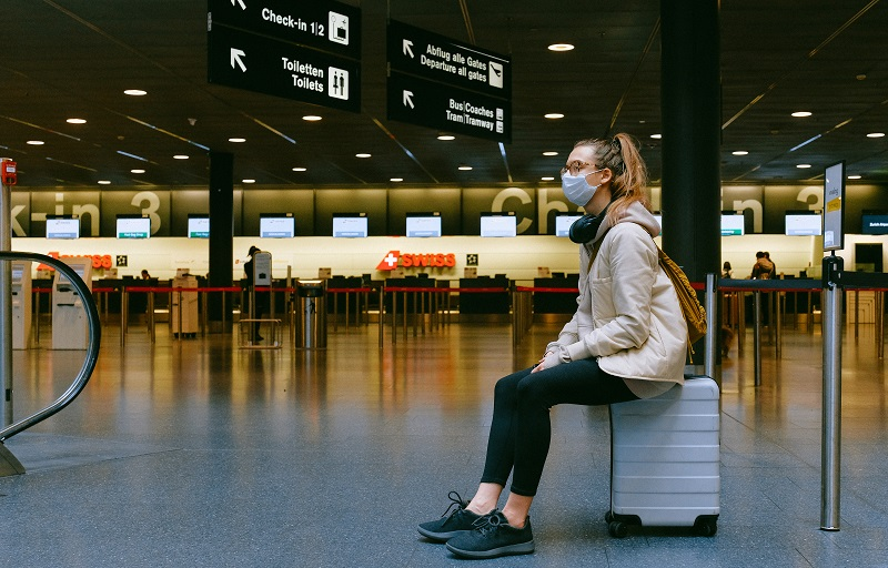 Woman sitting on a suitcase in the middle of an airport with a face mask on