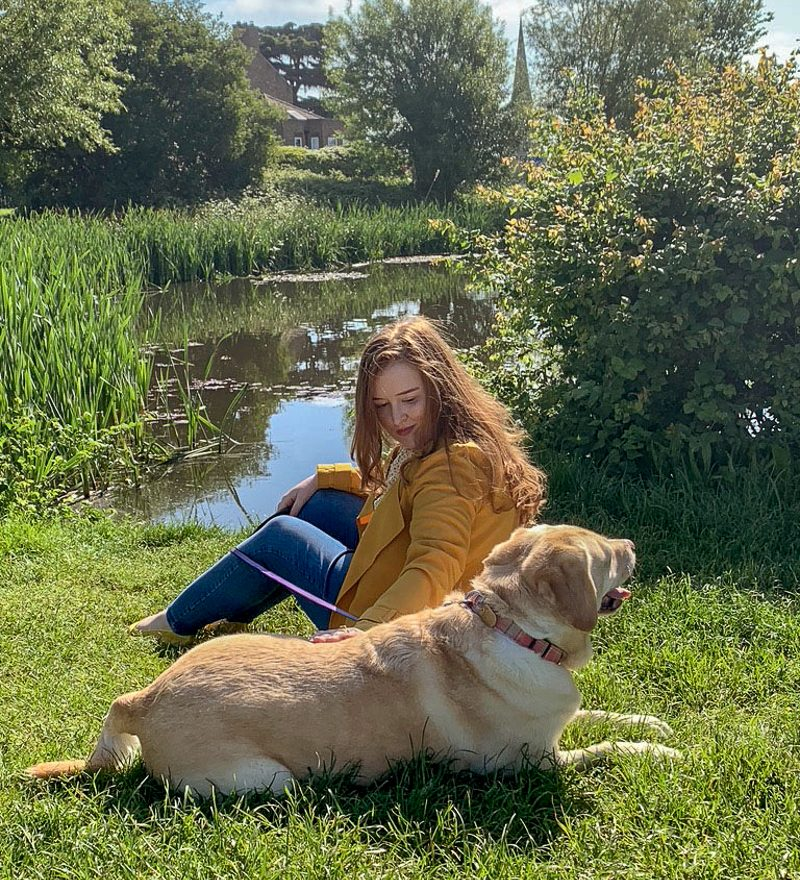 Emily sitting on grass with dog by a lake