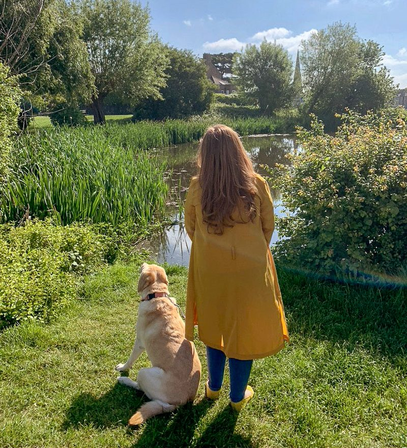 Emily standing on grass with dog looking at a lake