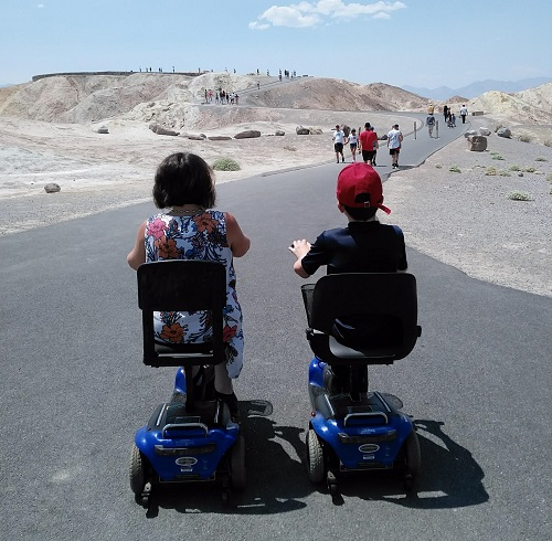 Emma and her son Archie on mobility scooters facing away from the camera in front of a dessert