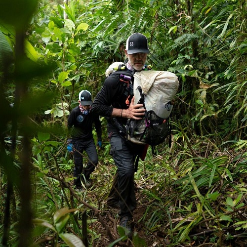 Hal Riley walking in a jungle carrying backpacks on his front and back