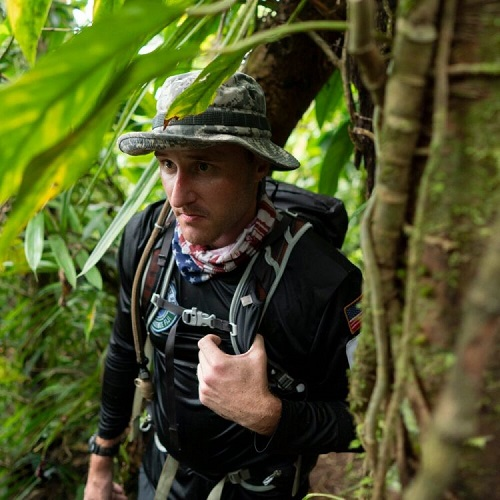Keith Knoop in the jungle with a backpack and hat on