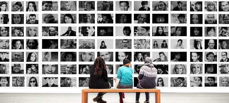 Three people sat on a bench in front of a wall of black and white portraits of people