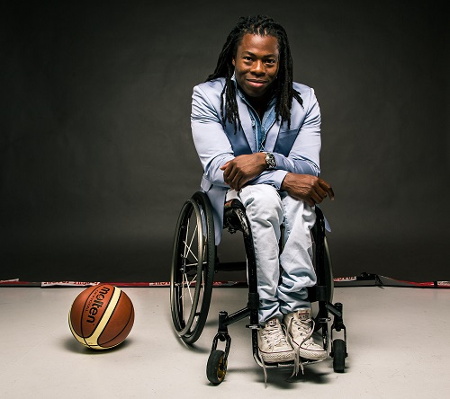 Ade Adepitan sat in his wheelchair in a blue suit jacket and white trousers on a black background with a basketball on the floor next to him