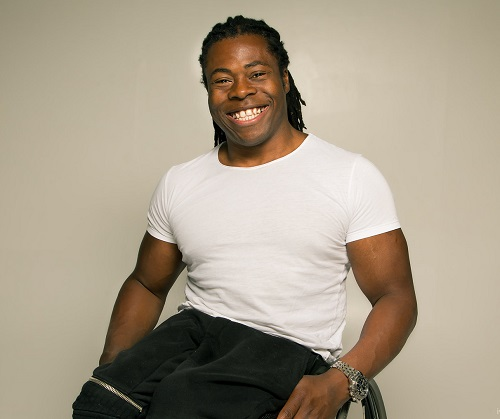 Ade Adepitan sat in his wheelchair in a white t-shirt with a basket ball on his lap