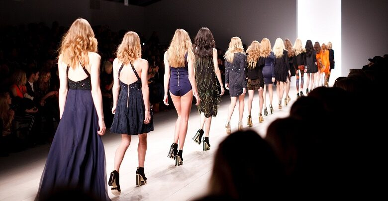 Catwalk with a line of women in black a blue dresses viewed from behind walking off the catwalk