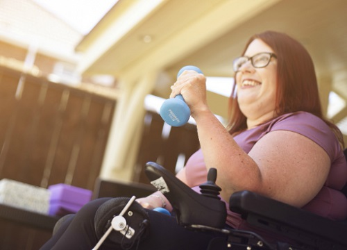 Tara doing an exercise class in her wheelchair using hand weights