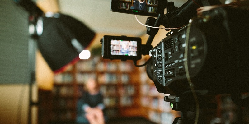 View from behind a camera filming a woman sat in a library