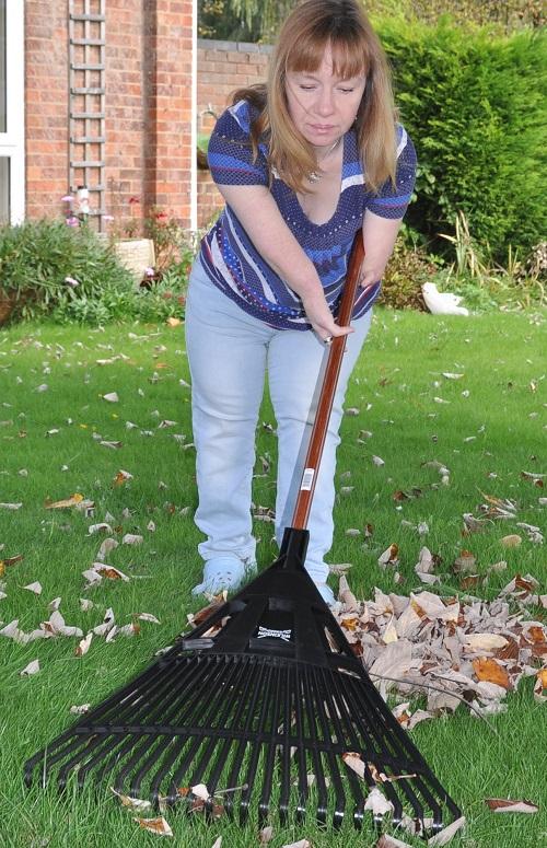 Disabled gardener Nikki Preston raking up leaves in her garden