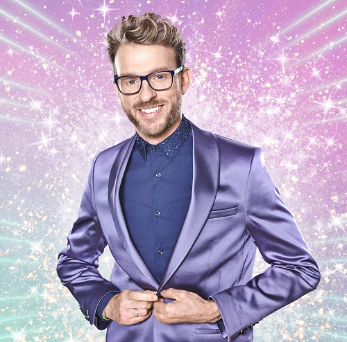 JJ Chalmers in a silk lilac suit and blue shirt on a pastel background with white stars