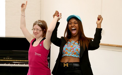 Jen in a pink top with Alexandra Burke cheering