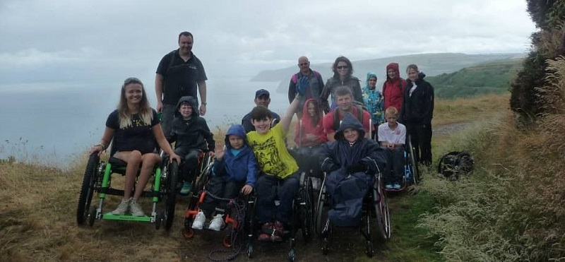 Laura May developing her outdoor activity skills with a group of wheelchair users on a walk with the sea in the background