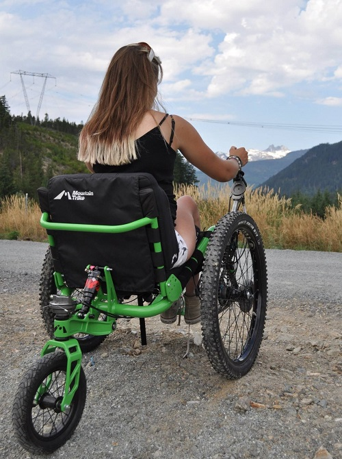 Laura May in her Mountain Trike wheelchair in Whislter on a mountain top looking at other cliffs