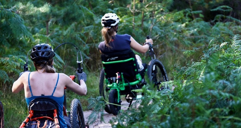 Laura May in her Mountain Trike wheelchair leading another woman in her wheelchair through shrubland