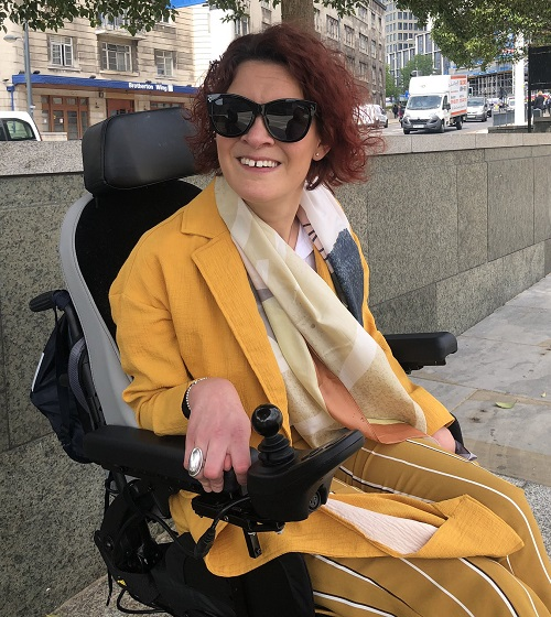 Dr Lucy Reynolds in a yellow jacket and skirt in her wheelchair on a pavement