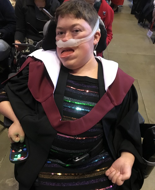 Stephanie in her wheelchair with her ventilator on wearing a black dress with coloured sequins