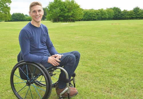 Steve Brown in a blue jumper and jeans sat in his wheelchair in a field with trees along the back