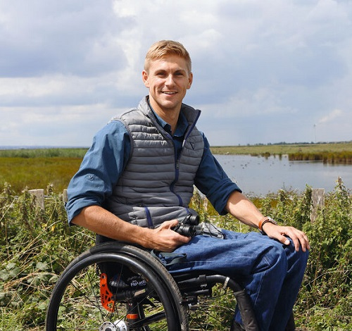 Steve Brown in a blue puffer jacket sat in his wheelchair in front of a lake and reeds