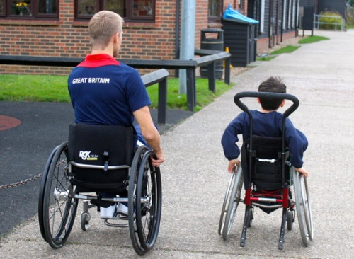 Steve Brown in his wheelchair next to a small boy in his wheelchair at a school wheeling away from the camera