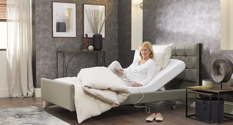 Woman sat in an adjustable bed with the back slightly raised