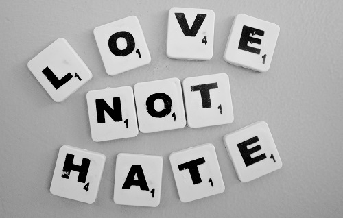Words love not hate spelt out in scrabble letters on a white table