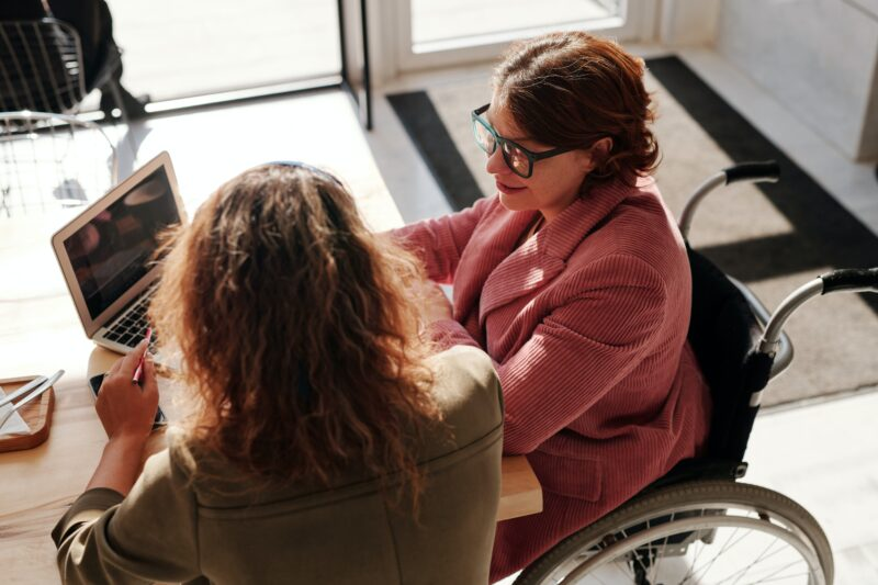 woman in wheelchair looks at computer with coworker