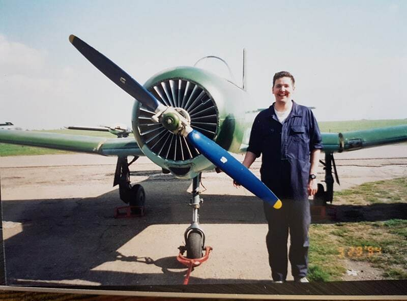 Darren in overalls standing next to green Airplane