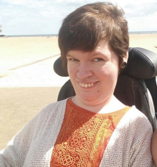 Gemma Orton in her wheelchair in a lacy orange top and white cardigain on a beach with the sea in the background