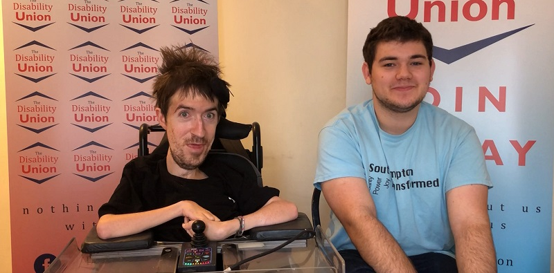 George Baker and Joel sat in front of logos for The Disability Union