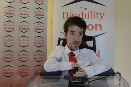 George Baker in his wheelchair with a white shirt and pink tie on in front of The Disability Union logos