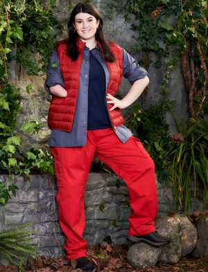'Hollie Arnold wearing a red puffer jacket, blue top, red trousers and walking boots standing in front of a wall covered in green leaves ready for I'm a Celebrity'.